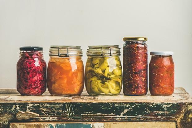 Őszi szezonális fermentált zöldség üvegekbe helyezve egy sorban a rusztikus konyhai fiók fölött, fehér háttér, másol hely, szögletes termés. Őszi otthoni ételkonzervek vagy konzervek